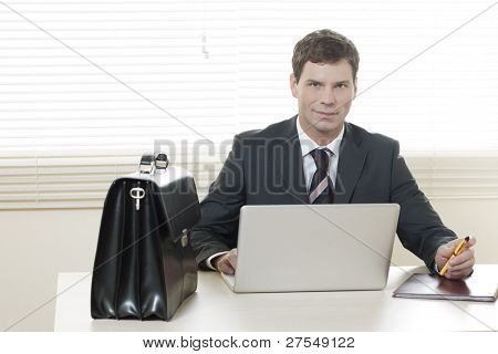 Businessman working on laptop in his office