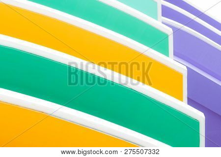 Closeup Facade Of Concrete Building. Yellow, White, Green, And Purple Building Texture Background Wi