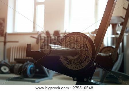 Closeup Of Metal Rack For Barbells In The Gym Club. Empty Metal Rack On The Background Of The Window