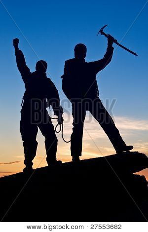 Silhouette Of Two Climbers With Hands Up