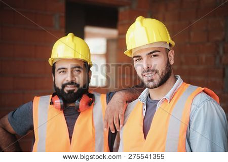 Happy Construction Workers Smiling At Camera In New Building