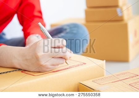 Women Writing Down For The Customer Address On The Parcel Box Close Up.  E-commerce In Modern Busine