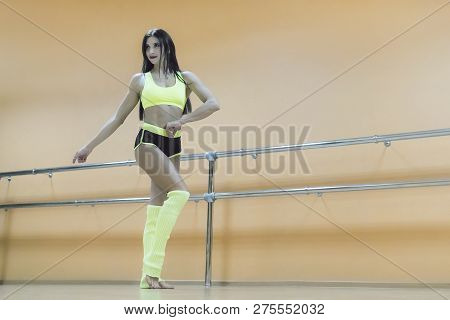 Smiling Brunette Dancer Posing Against Choreographic Machine In Empty Dance Hall. Beautiful Sporty P