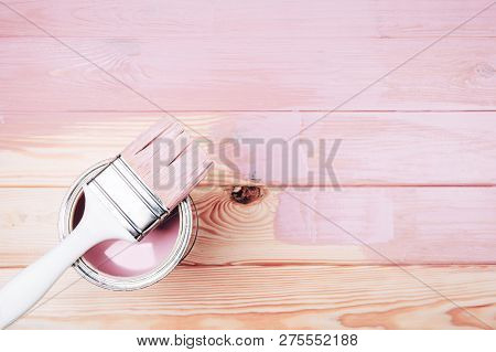 Open Can Of Pink Paint With White Brush On Painting Wooden Board. Renovation Concept.
