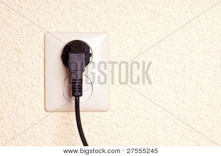Outlet with plug against a textured backgrund