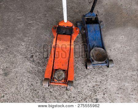 Hydraulic Heavy Car Jacks On Garage Floor Close Up.
