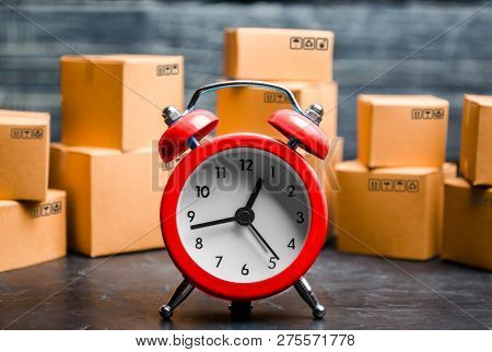 Cardboard Boxes And Red Alarm Clock. Time Of Delivery. Limited Supply, Shortage Of Goods In Stock, H