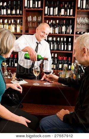 Wine bar senior couple enjoy drink smiling barman pour glass
