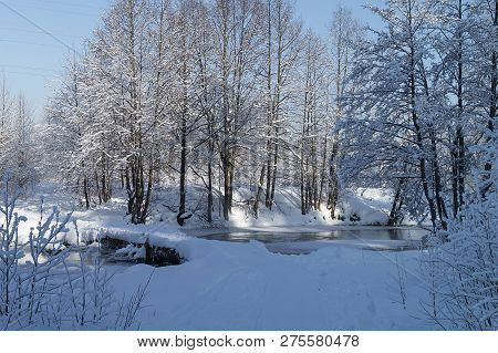 Winter Landscape With Stream And Footbridge In Rural Terrain On Background Blue Sky