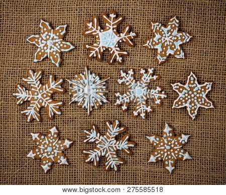 Decorated Snowflake Christmas Gingerbread Cookies On Brown Burlap Canvas Background
