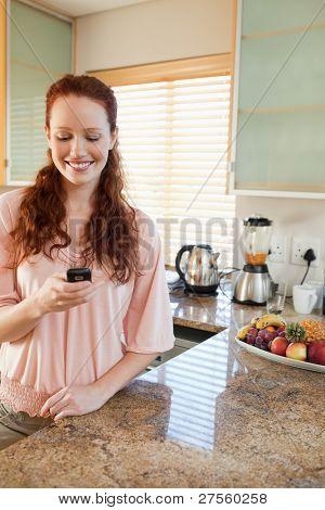 Femme souriante, écrire des SMS dans la cuisine