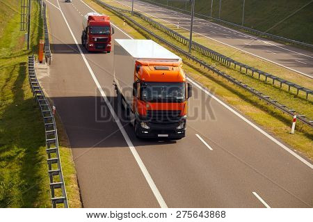View From Above. A Red Truck With A Semi-trailer And A Tanker Driving On A Fast-moving Road.