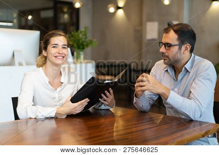 Two Colleagues During Corporate Meeting. Business Man And Smiling Woman With Open Folder Sitting At
