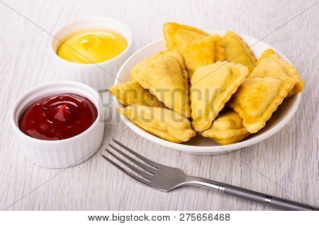Small Fried Savory Pies In White Plate, Bowls With Mayonnaise And Ketchup, Fork On Wooden Table