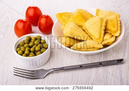 Small Fried Savory Pies In White Plate, Fork, Bowl With Green Peas, Red Tomatoes On Wooden Table