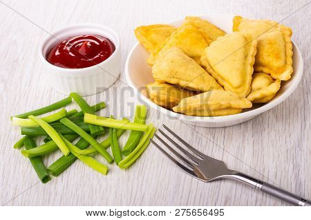 Small Fried Savory Pies In White Plate, Fork, Bowl With Ketchup, Chopped Green Onion On Wooden Table