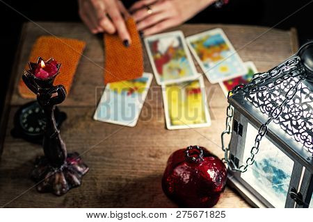 Fortune-telling On Traditional Tarot Cards On The Old Wooden Table With A Lantern And A Candle. Sele