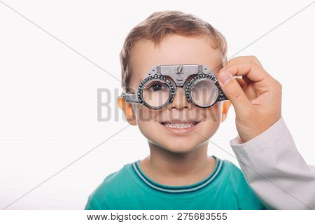 Optometrist Checking Vision Of A Little Cheerful Boy Using Trial Frame