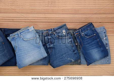 Different blue Jeans. Stylish clothes. Selective focus on wooden background