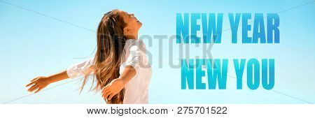 New Year New Start happy woman with open arms in freedom and carefree banner panorama. Girl healthy, well-being concept on blue background.