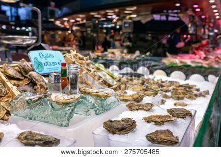 Barcelona, Spain - March 27, 2018: Opened fresh oysters on ice with lemon at the Mercat de Sant Josep de la Boqueria, a large public market in the Ciutat Vella district in Barcelona, Spain.