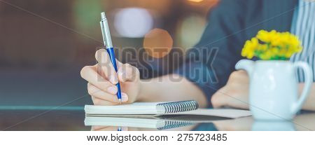 Woman Writing On A Notebook With A Pen In The Office.web Banner.