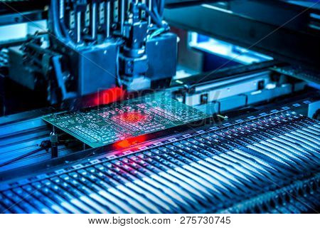 Electronic circuit under surface-mounting machine. Shot in red and blue tints. Surface-mount technology as a producing of electronic circuits. Components placed onto the surface of printed elements.
