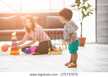 Happy Asian Family, Young Beautiful Mother In Pink Blouse, Sitting On Floor, Playing With Son, Adora