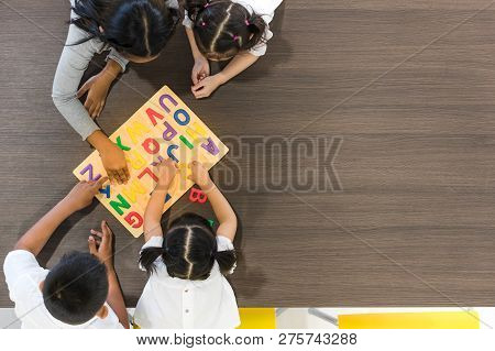 Flat Lay Shot Of Asian Teacher Play Colorful Alphabet  Wooden Blocks  With Asian Student Together, C