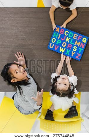 Flat Lay Shot Of Asian Teachers Play Colorful Alphabet Puzzle Toy With Asian Students Together, They