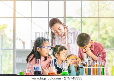 Science Teacher Teach Asian Students In Laboratory Room, Boy  Look Through Microscope, Colorful Test