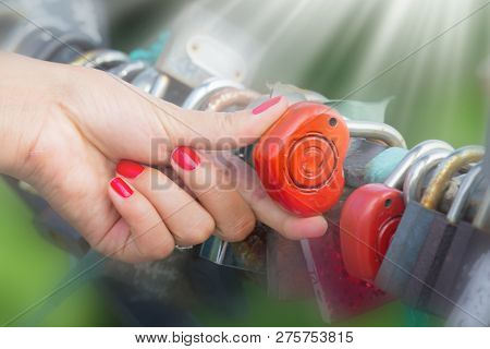 Girl Hand With Locks Of Lovers On The Bridge At Sunny Day