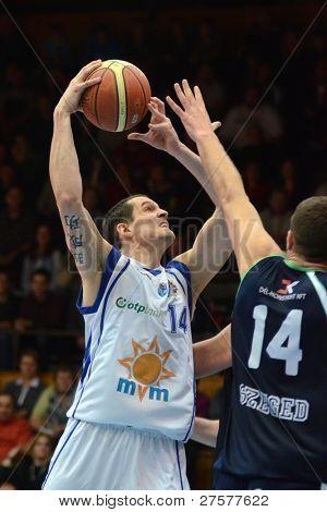 KAPOSVAR, HUNGARY - DECEMBER 10: Jozsef Lekli (in white) in action at a Hungarian Championship basketball game Kaposvar (white) vs. Szeged (blue) on December 10, 2011 in Kaposvar, Hungary.