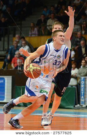KAPOSVAR, HUNGARY - DECEMBER 10: Nik Raivio (in white) in action at a Hungarian Championship basketball game Kaposvar (white) vs. Szeged (blue) on December 10, 2011 in Kaposvar, Hungary.