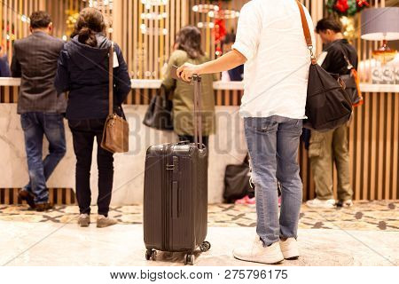 Man Holding Passport With Suitcase Waiting To Checking In At Hotel Reception.