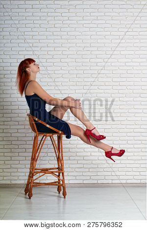 Elegant Beautiful Leggy Girl In A Short Sexy Dress Sits In A High Wicker Chair