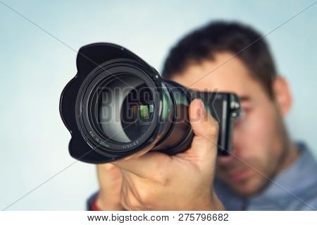 Male Photographer Hold Camera In His Hands. Mirrorless Camera Close Up In The Hand Of A Young Man On