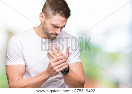 Handsome man wearing white t-shirt over outdoors background Suffering pain on hands and fingers, arthritis inflammation