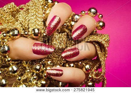 Female Hand With Gold Glittered Pink Nails Is Holding Gold Pearl Jewelry On Pink Background, Nail Ca