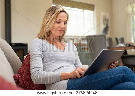 Beautiful mature woman sitting on couch and using digital tablet. Smiling lady browsing internet over tablet at home. Middle age woman holding computer at home.