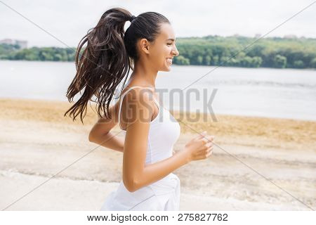 Beautiful Portrait Of Brunette Smile Young Woman Runner In Profile, Running And Jogging In City Park