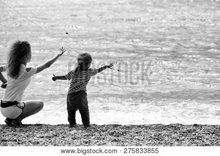 Mother Young Woman And Son Baby Boy Sit On Pebble Beach Near Blue Sea Windy Weather On Natural Backg