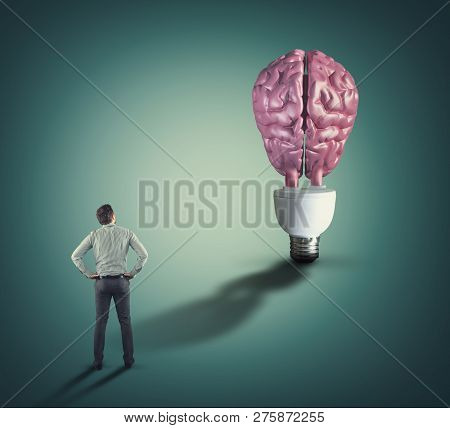 Businessman Looks To A Lightbulb With A Human Brain.