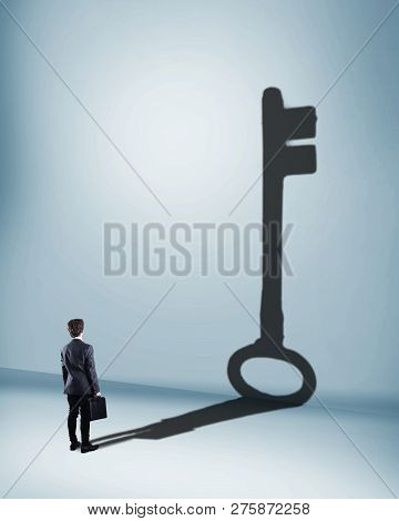 Businessman Standing In Front Of A Wall With His Shadow As A Key.