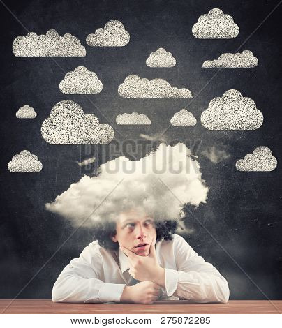 Thoughtful Man With An Cloud On His Head Against A Blackboard Drawn With Clouds.