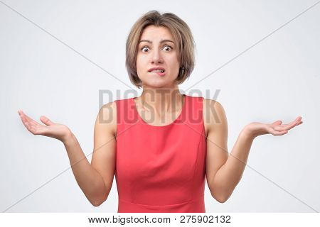 Woman In Blue Clothes Shrugging Her Shoulders, Expressing Doubt, Uncertainty Or Indifference