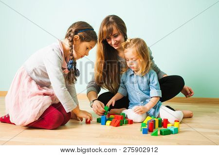 Young Nanny Playing With Kids While Babysitting