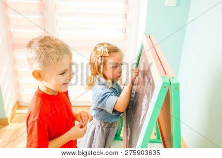 Happy Kids Writing On A Blackboard At The Kindergarten