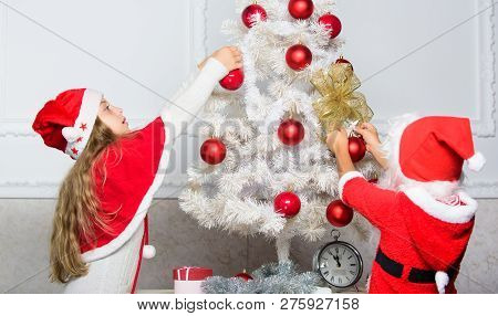 Siblings busy decorating. Boy and girl decorating tree. Cherished holiday activity. Kids in santa hats decorating christmas tree. Family tradition concept. Children decorating christmas tree together poster