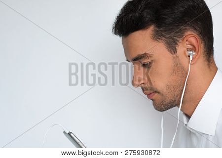 Close Up Sideways Portrait Of A Handsome Attractive Young Man In White Shirt With Earphones Holding